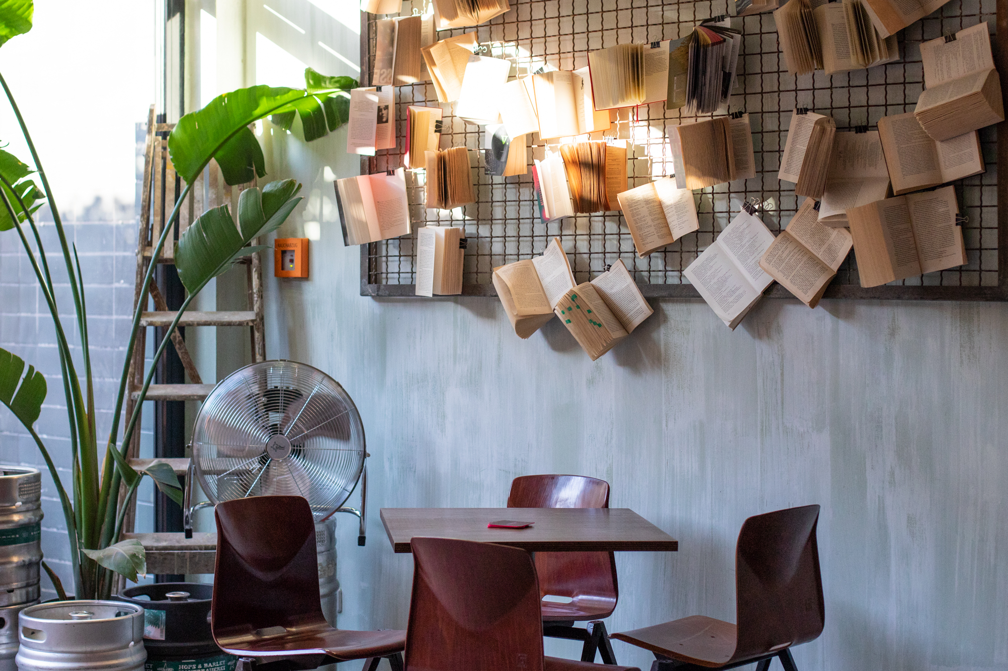 Table, chairs and books at Muted Horn, a craft beer bar in Berlin Neukölln